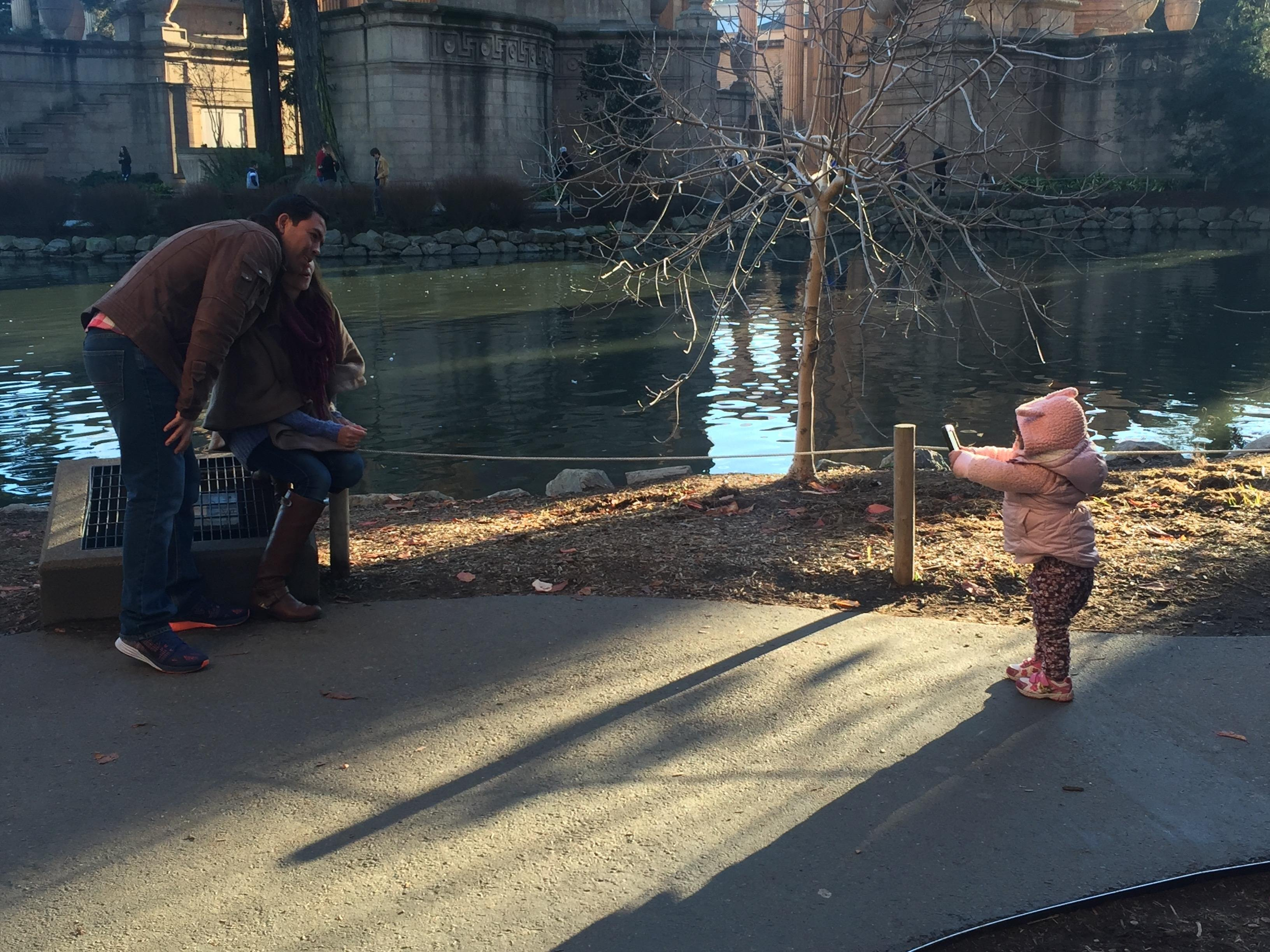 Couple getting their toddler to take a photo of them
