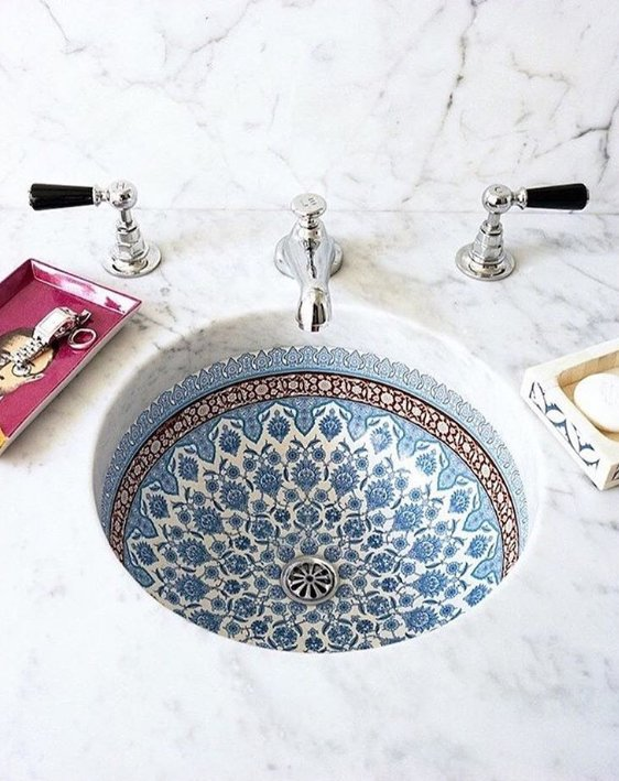 Porcelain sink with a delicate pattern and a thick marble countertop