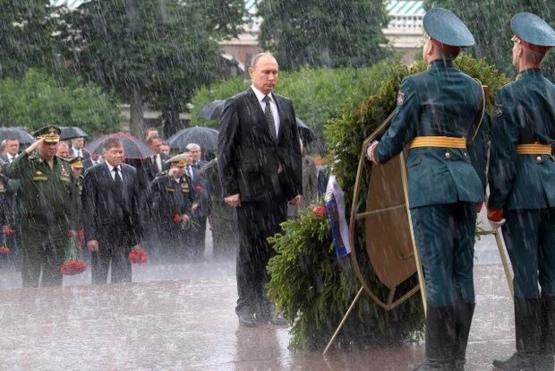 How a Russian President honors his countries troops during a rain storm.