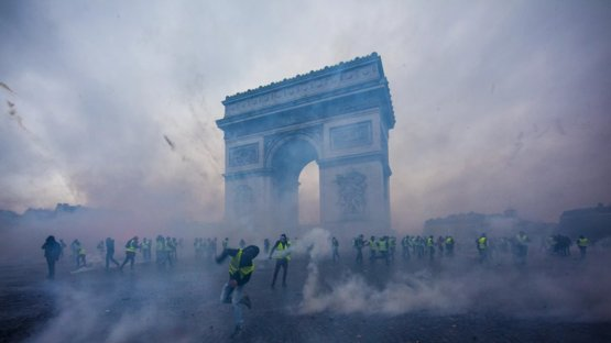 Tear gas surrounds protesters as they clash with riot police in Paris on December 1, 2018.