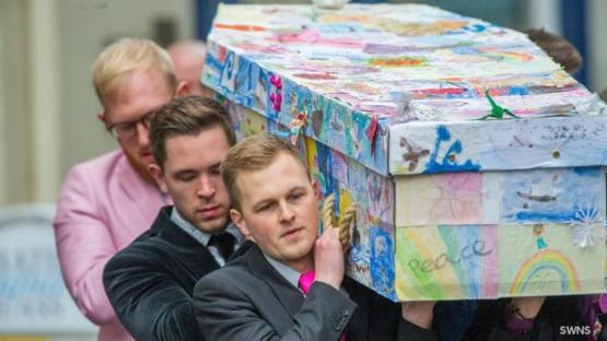 A former primary school head has been laid to rest in a coffin covered in drawings by her pupils.