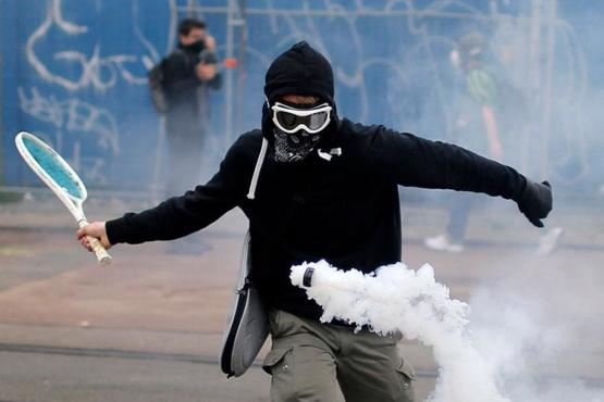 Protester uses tennis racket to return gas canister during government protest, France, 2016.