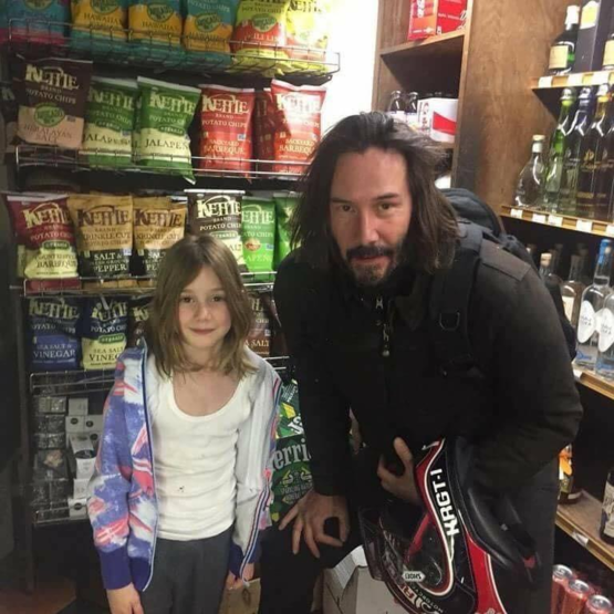 Keanu Reeves taking a photo with a little girl