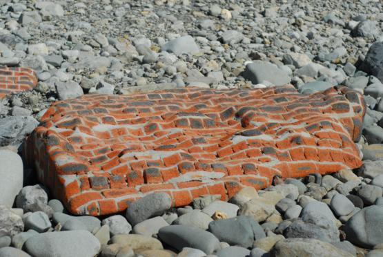 A piece of brick wall shaped by the ocean surf