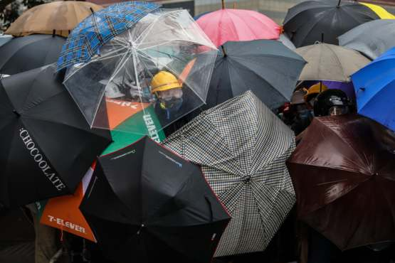 Protesters shield themselves with umbrellas against pepper spray used by the police outside the government headquarters in Hong Kong
