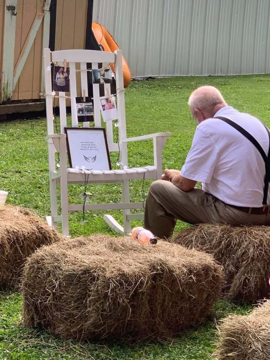 The bride set out a chair for her late grandmother. Her grandfather sat down and ate next to it