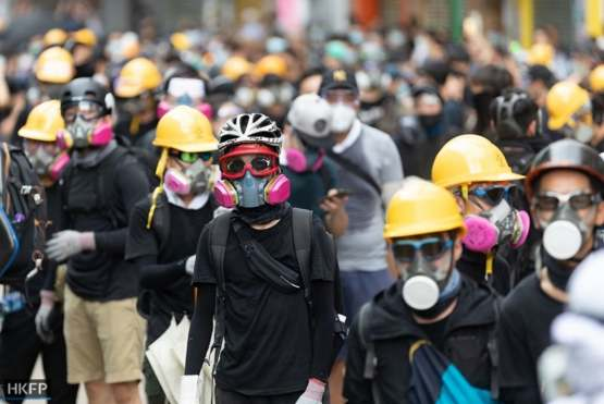 Hong Kong protestors wear helmets and gas masks to protect themselves against the police