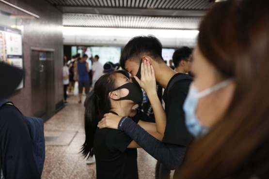 A young Hong Kong couple share a moment after finding respite from tear gas and advancing ranks of riot police in a metro station.
