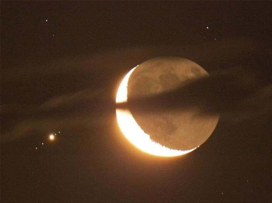 Crescent moon and Jupiter with four of its moons.