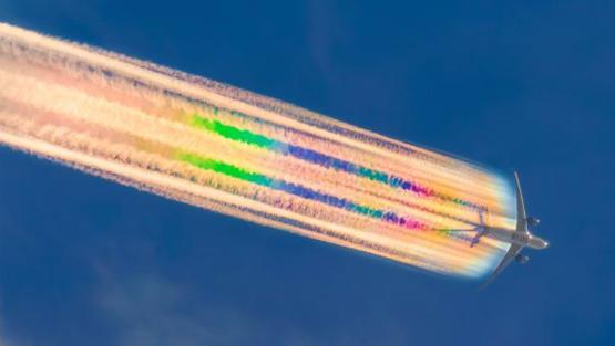Photographer captures airplane's technicolor rainbow trail that occurs when contrail crystals are perfectly aligned with sun