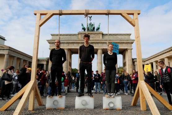 Activists standing on blocks of ice in the Climate strike. Berlin, Germany