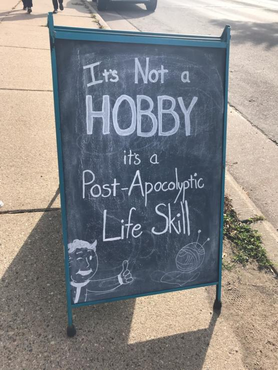 This sign outside of a knitting shop