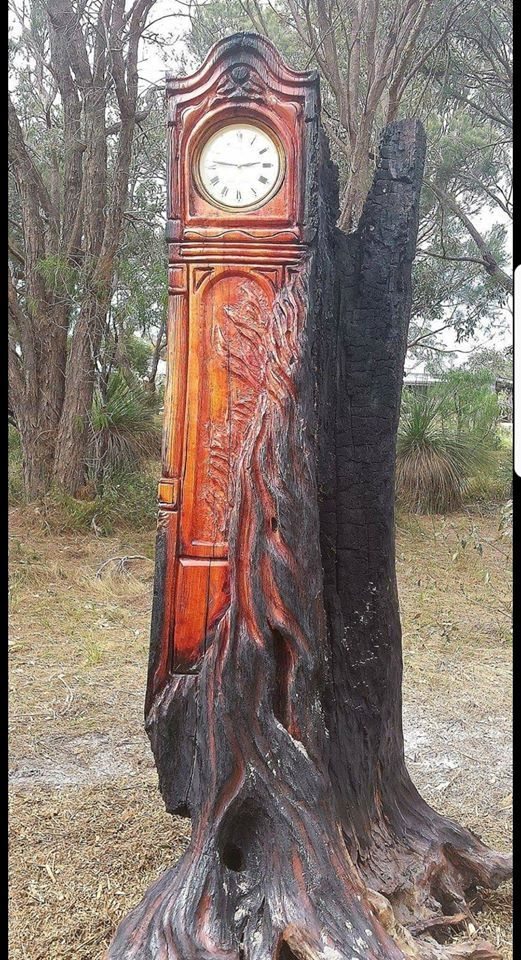 Grandfather clock carved into burnt tree trunk
