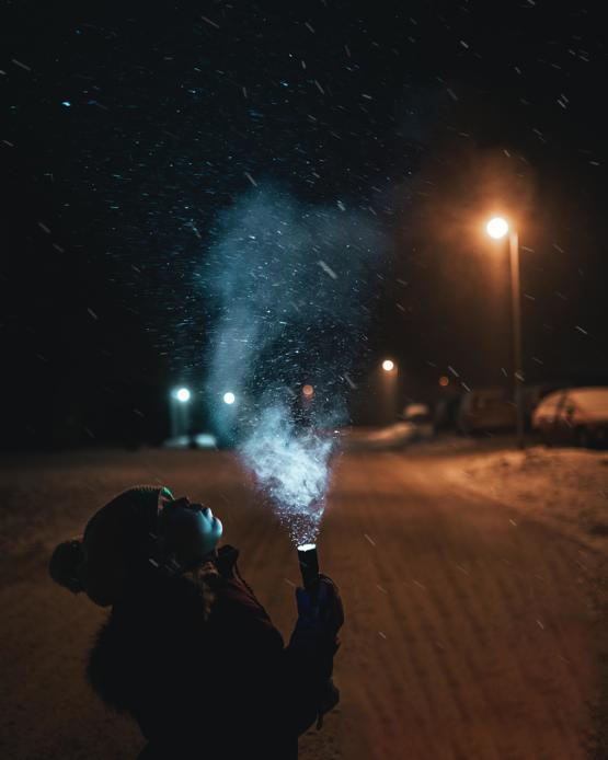 My daughter holding a flashlight in snowy weather.