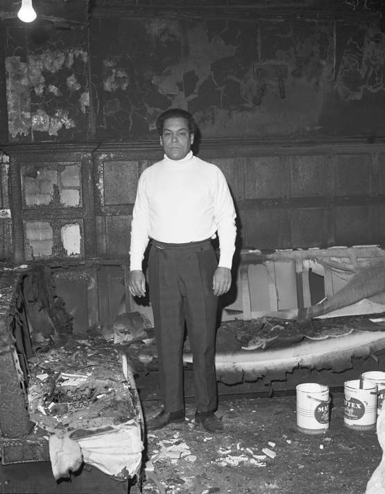 London's first black pub owner, standing in his pub that was burnt down by racist fire attack (1965)