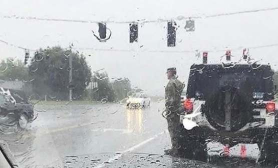A funeral procession drove past and this solider left his car to stand at attention in the rain.