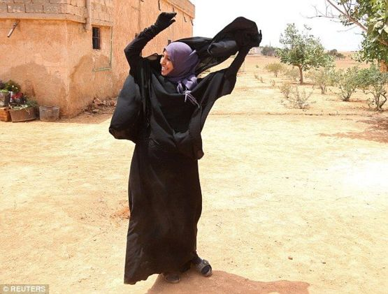 Liberation: A woman removes her niqab after her city is freed from Isis control