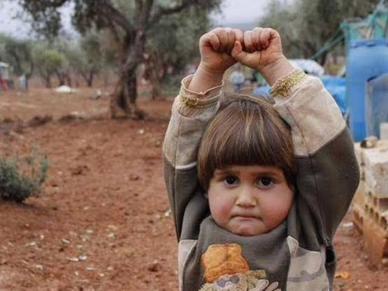 Syrian child photographed 'surrendering to camera because she thought it was a gun'.