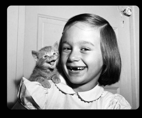This kitten smiling bigger than the little girl for a photo, 1955.