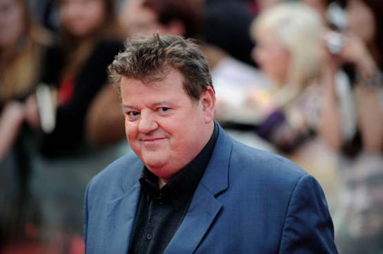Hagrid without his beard, cleaned up in a suit