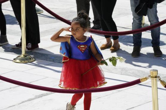 A girl dressed in a Supergirl costume pays her respects at the casket bearing the remains of RBG