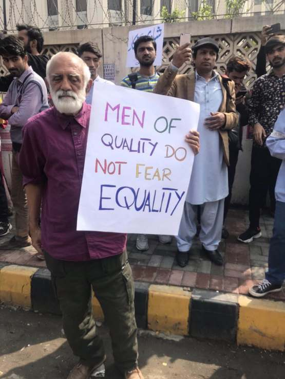 A sign held by an old man at a women's march in Karachi