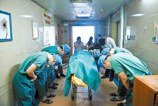 Chinese doctors bowing to a child whose organs saved several lives before he died of brain cancer