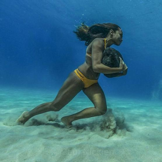 Hawaiian Surfer Ha'a Keaulana training for large waves by carrying a 50lb stone underwater.