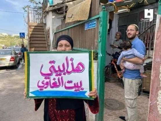 """Palestanian holds a sign saying """"This is my home"""" in front of the jewish family taking over her home"""