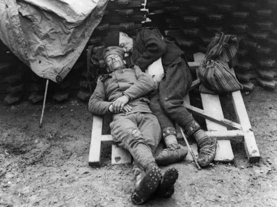 A Serbian soldier naps with his father who came to visit him on the front line 1914/1915