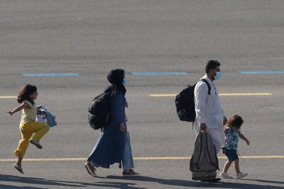 A girl skips across the tarmac as she and her family evacuated from Afghanistan arrive in Belgium