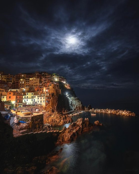Dramatic clouds floating under a full moon over Manarola, Italy.