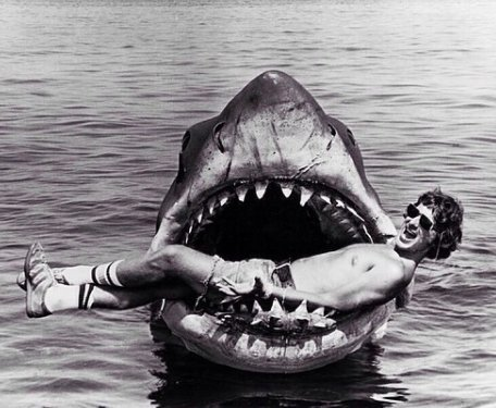 """Steven Spielberg lying in the mouth of """"Bruce the shark"""" on the set of Jaws, 1975"""