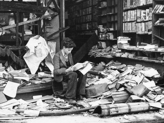 A boy reading in a ruined bookshop in London, after a night of heavy bombing. October 1940