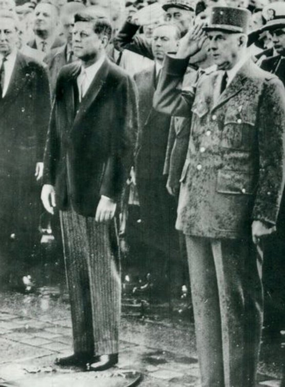 May 1961, JFK and de Gaulle stand in the rain, honoring soldiers who gave their lives.