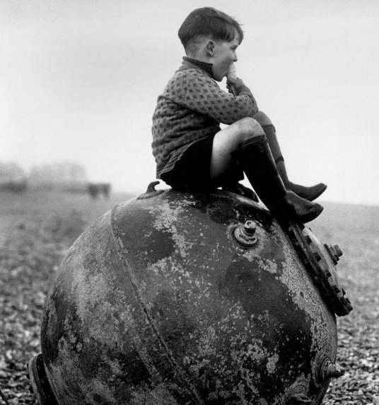Boy sitting on a sea mine, Kent, England, 1945.