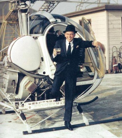 Frank Sinatra stepping off of a helicopter with a drink in his hand, 1964