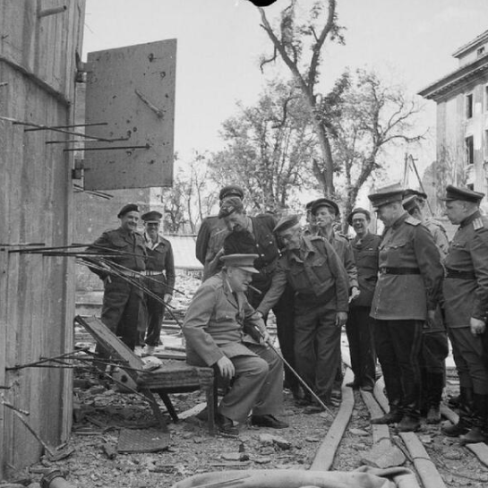 Winston Churchill sits on one of the damaged chairs from Hitler's bunker in Berlin, 1945