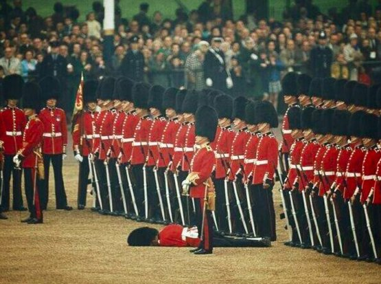 Guardsman fainted during a ceremony, but other guards kept their attention. London, 1966