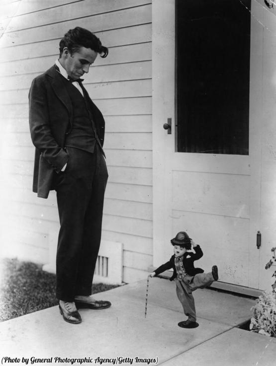 Charlie Chaplin looks down at a knee-high doll of himself. Happy Birthday Charlie!