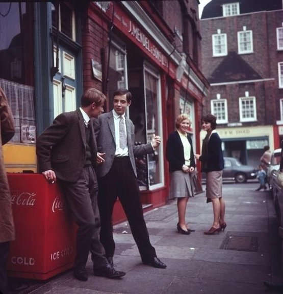 Flirting outside of J. Mendel & Sons, London, 1960s.