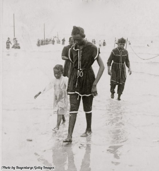 Mother walks her child on the beach at Coney Island, 1896.