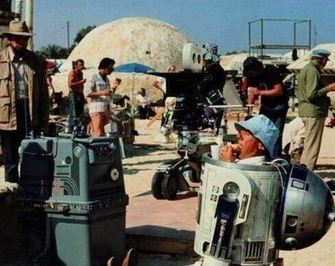 R2D2 (Kenny Baker) eating a sandwich on the set of Star Wars.