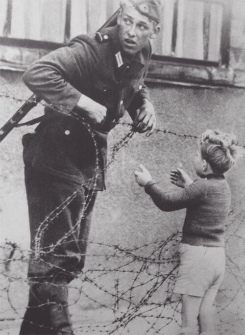 East German soldier helping a boy cross the new Berlin Wall, to reunite with his family. 1961.