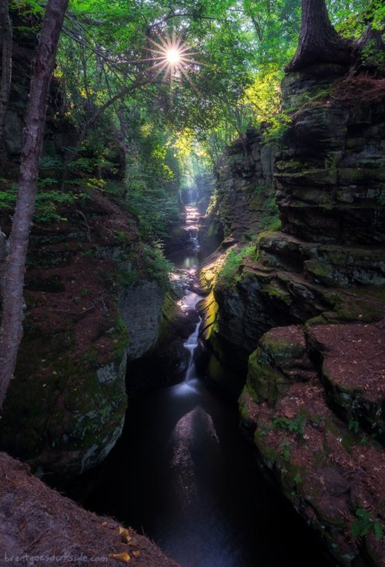 Light bursts through the trees onto the waterfalls of Skillet Creek in Pewits Nest, Wisconsin
