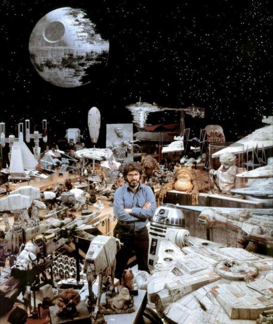 George Lucas surrounded by Star Wars props.