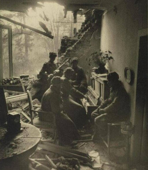 Russian soldiers playing piano in a wrecked living room in Berlin, 1945.