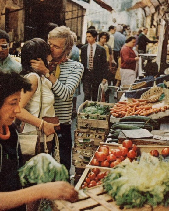 Young lovers kiss amid the crowds of a Parisian market, France, 1972. Photograph by Gordon Gahan.