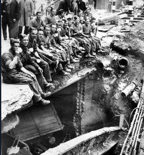 Engineers of the British Army drink their tea on the edge of a bomb crater in London, 1940.