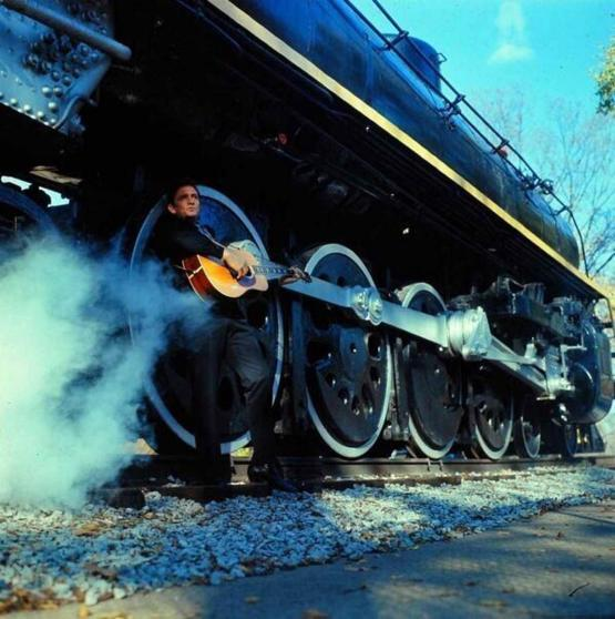 Johnny Cash leaning on a train. Photo by Michael Rougier.